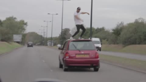 Dude dances on top of fast moving car on highway