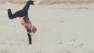 Orange shirt kid does handstand on stand and falls on blonde head