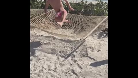 Guy tries to be cool but falls off hammock into sand