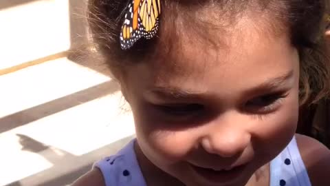 Monarch butterfly hangs out in little girl's hair