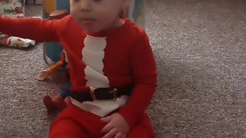 Toddler adorably unaware of unwrapped Christmas gifts directly behind him