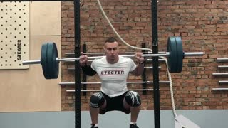 Man Is Doing Barbell Squats On A Seesaw