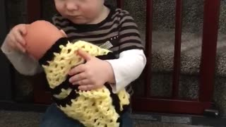 Toddler prepares to become big brother by caring for doll - Video