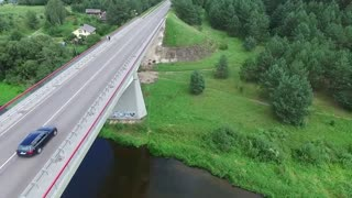 Flying drone over the bridge over the river