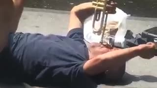 A man in blue playing trumpet on street floor - Video