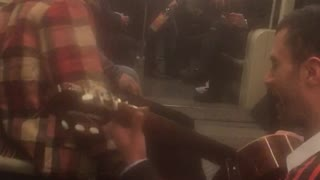 Man in red flannel and man with guitar singing on train - Video
