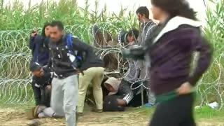 Migrants climb under barbed wires to reach Hungary - Video
