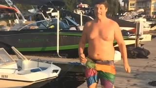 Chunky guy slips on pier while trying to run to water for a dive - Video