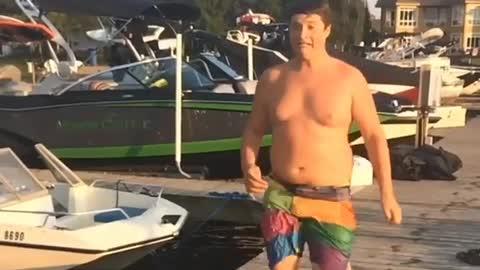 Chunky guy slips on pier while trying to run to water for a dive