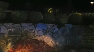 Guy runs off of rocks into blue lit crescent pool dive water - Video