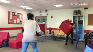 Guy and girl run at each other with red block chairs girl runs into wall - Video