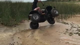 Man on black four wheeler flips