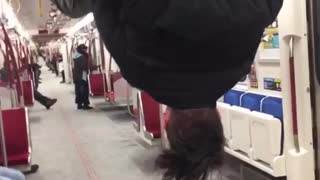 Man hanging and flipping from bar on train