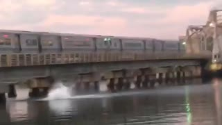 Two people jump from moving train on bridge to water below - Video