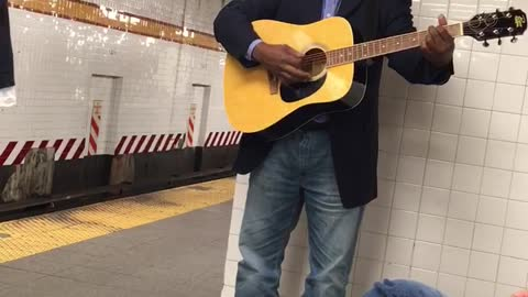 Man in blue suit playing guitar in station