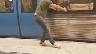 Man in green pretends to stop subway train with hands - Video