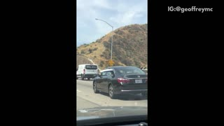 White surfboard out of back windows of black honda freeway