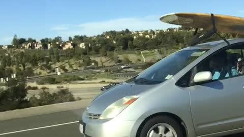 Yellow surfboard on silver prius