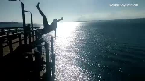 Man jumps off pier and lands on his side