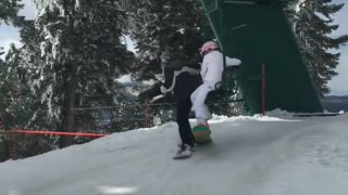 Man and woman fall on top of each other off ski lift