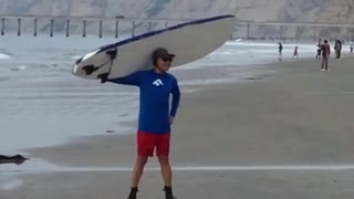 Man in blue carrying white surfboard for picture - Video