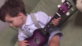 Cute baby playing ukulele