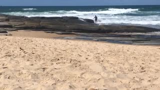 Guy fishing on rocks by ocean gets hit with wave and falls in - Video