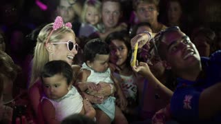 Paris Hilton holds twin babies at charity event