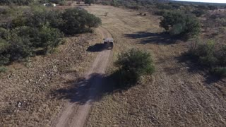 Drone following a military style hummer on a dirt road. - Video