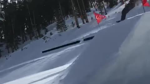 Skier jumps off big ramp and lands on front of skis, falls down slope