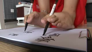 Woman writes with hands and feet simultaneously - Video