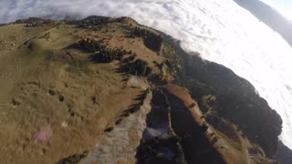 Wingsuit flying and paragliding over sea of clouds