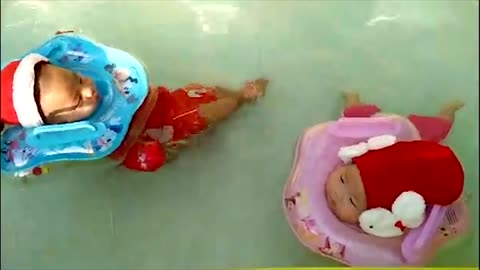 Twin babies swim adorably while wearing Santa outfits
