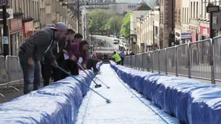 Artist turns central street into giant water slide - Video