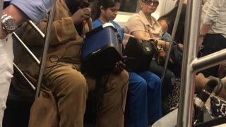 Guy in tan suit singing from blue speaker on subway