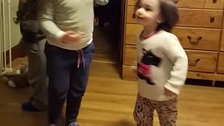 Three kids spin around on wood floor one falls down - Video