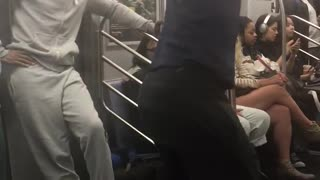 Guy dark blue shirt dancing on pole music subway