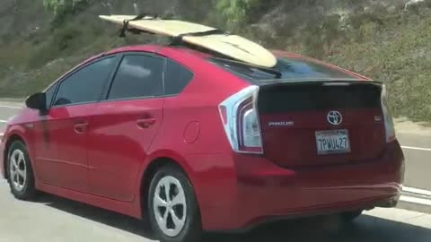 Red prius surfboard on roof