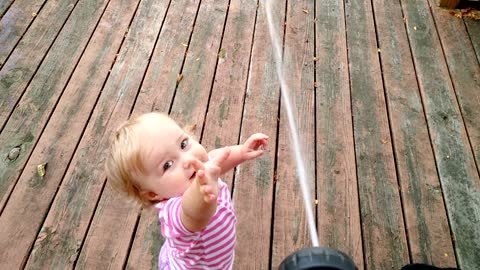 Toddler adorably entertained by water hose