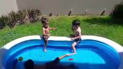 Two kids on inflatable pool one kid falls off
