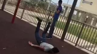 Guy does flip on play ground handle bars and faceplants