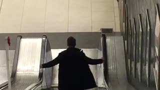 Jacket guy walking down escalator waves hands back and forth - Video