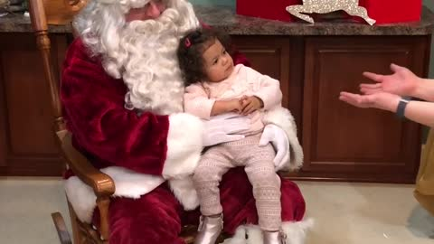 Little girl refuses to leave Santa's lap
