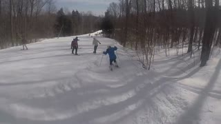 Blue jacket skier falls snow hump - Video