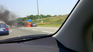 BMW in flames on highway shoulder
