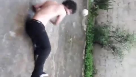Shirtless man black pants kicks ball falls back
