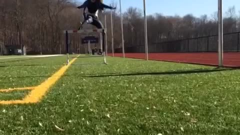 Slo-mo video girl jumps over hurdle, trips over it, and falls down