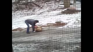 Man struggles to take groceries up icy hill