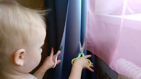 Funny baby decided to cut the curtains