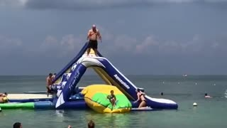 Guy jumps and tosses girl into water - Video